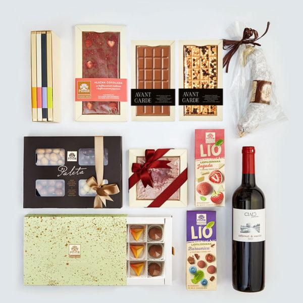Paket sa Avant Garde čokoladama, bombonjerom draže bombona, čokoladnom kobasicom, voćnim dražejima, pralinama i flašom crnog vina