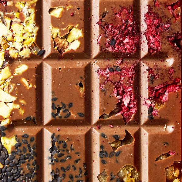 Mlečna čokolada sa liofilizovanom malinom, pistaćima, narandžinom korom, crnim susamom i kakao zrnom